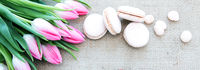 Mother's day background with tulips bouquet and pink macarons.