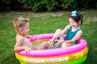 Kids having fun party swimming in back yard pool. Funny children bathing in the outdoor pool. Happy children playing in the water. babies Having Fun In Garden Paddling Pool