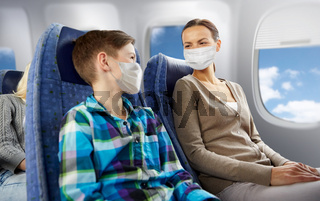 mother and son in masks traveling by plane