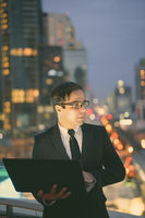 Handsome Persian businessman against view of the city at night
