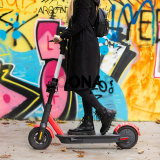 Trendy teenage girl riding public rental electric scooter in urban city environment at fall. New eco-friendly modern public city transport in Ljubljana