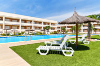 Torrevieja, Spain - June 2, 2020: Empty area with deckchairs and swimming pool during sunny summer day. Travel and summer holidays concept