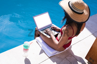 Mixed race woman at home using laptop by the pool