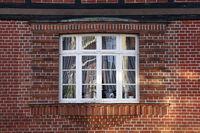 altes Sprossenfenster in einer Backstein-Fassade