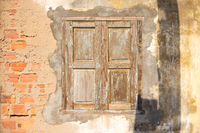 A closed weathered wooden shutter window.