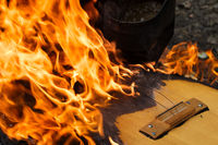 Part of guitar in flame on campfire