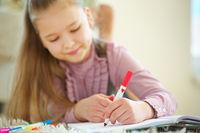 Kind hält roten Stift in der Hand