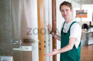 Glazier presenting glass doors in showroom