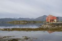 Rotes Holzhaus an einem Fjord