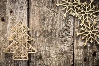 Gold Christmas tree decorations on grunge wood