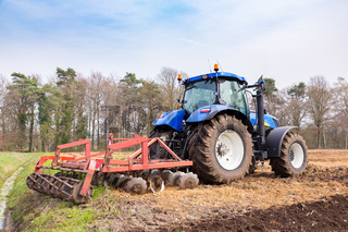 Tractor tills the ground with a harrow in spring
