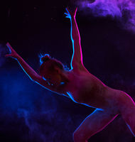 Graceful girl dancing in color powder cloud