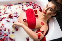 Sexy brunette in red bikini take a milk bath with rose petals
