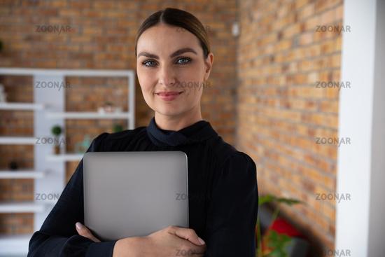 Portrait of woman holding a laptop