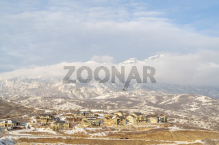 Houses with view of snowy mountain partially covered by clouds in winter