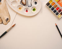 Blank watercolor paper sheet with utensils