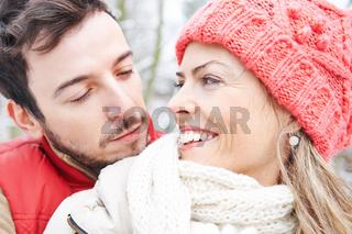 Paar kuschelt draußen im Winter