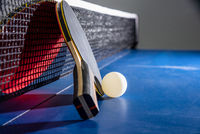 Closeup red table tennis paddle white ball and a net