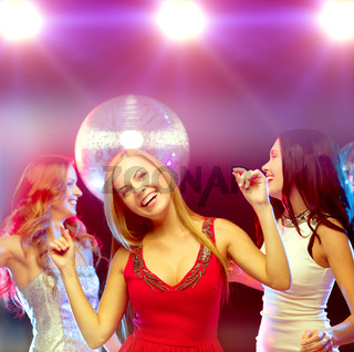 three smiling women dancing in the club