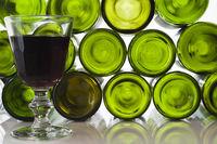 Glas mit Rotwein vor leeren Weinflaschen