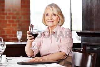 Seniorin trinkt Rotwein im Restaurant