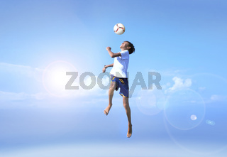 Young boy in a jump, football player doing amazing makes a headbutt a background of blue sky