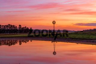 Windmill sits on farm land with beautiful sunrise sky