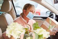 Frau mit Mundschutz in Auto Innenraum prüft Paket