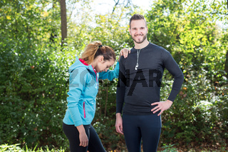 Shot of young couple of runners taking a rest after running training, Man and woman standing outdoors in morning after a jog