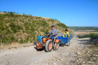 Mini tractor with passengers at dirt mountain road at Northern Moldova