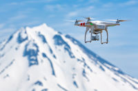 Quadcopter flying on background volcanic peak, aerial videography world around from bird's eye view