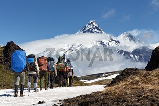 Group of hikers climbing in mountain on background volcanoes of Kamchatka Peninsula