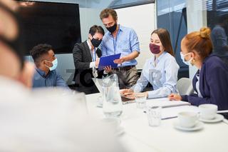 Start-Up Team mit Mundschutz in einem Meeting