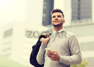 happy young man with smartphone and bag in city