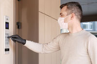 Man in face mask and gloves dials the code on the intercom and going in porch of his apartment. Pandemic covid-19 concept