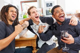 Männer als Freunde jubeln gemeinsam beim Fußball oder Sport schauen