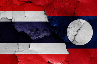 flags of Thailand and Laos painted on cracked wall
