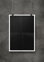 Black folded poster hanging on a concrete wall with clips