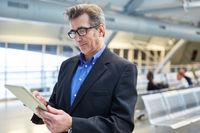 Geschäftsmann mit Tablet Computer am Flughafen