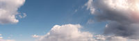 Blue cloudy sky background with warm sunny tonings. Wide-angle panoramic natural background, banner format