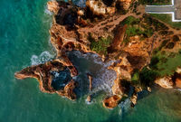 Aerial photo view directly from above Ponta da Piedade headland with group of rock formations yellow-golden cliffs along limestone coastline, Lagos town, most famous touristic attractions of Portugal