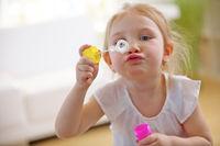 Mädchen pustet Seifenblasen im Kinderzimmer