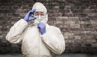 Chinese Man Wearing Hazmat Suit, Goggles and Mask with Brick Wall Background