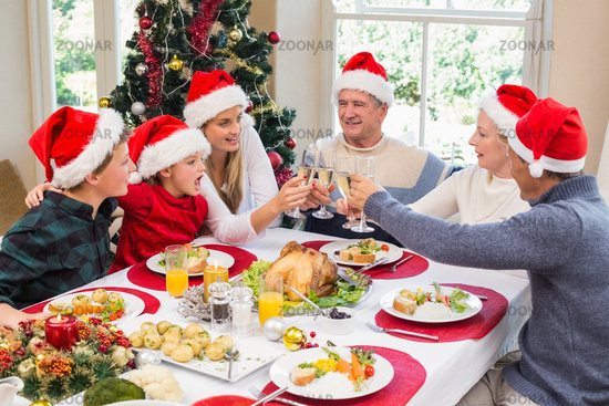 Multi generation family in santa hat toasting each other