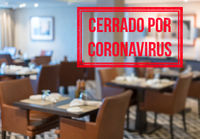Modern restaurant with tables closed and sign in spanish saying Closed due to Coronavirus