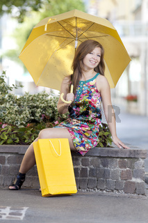 Junge Frau mit Schirm und Einkaufstuete