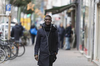 Handsome Black Man with Earphones and Hand in Pocket Posing on Sidewalk