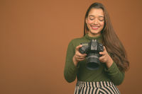 Young beautiful Indian woman with camera against brown background