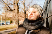Man leans against a fence outside and enjoys the sun in the cold season. Contemplation, serenity and relaxing concept.