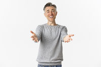 Image of happy and pleased middle-aged man with gray hair, reaching hands forward to hug or welcome someone, smiling relieved, standing over white background